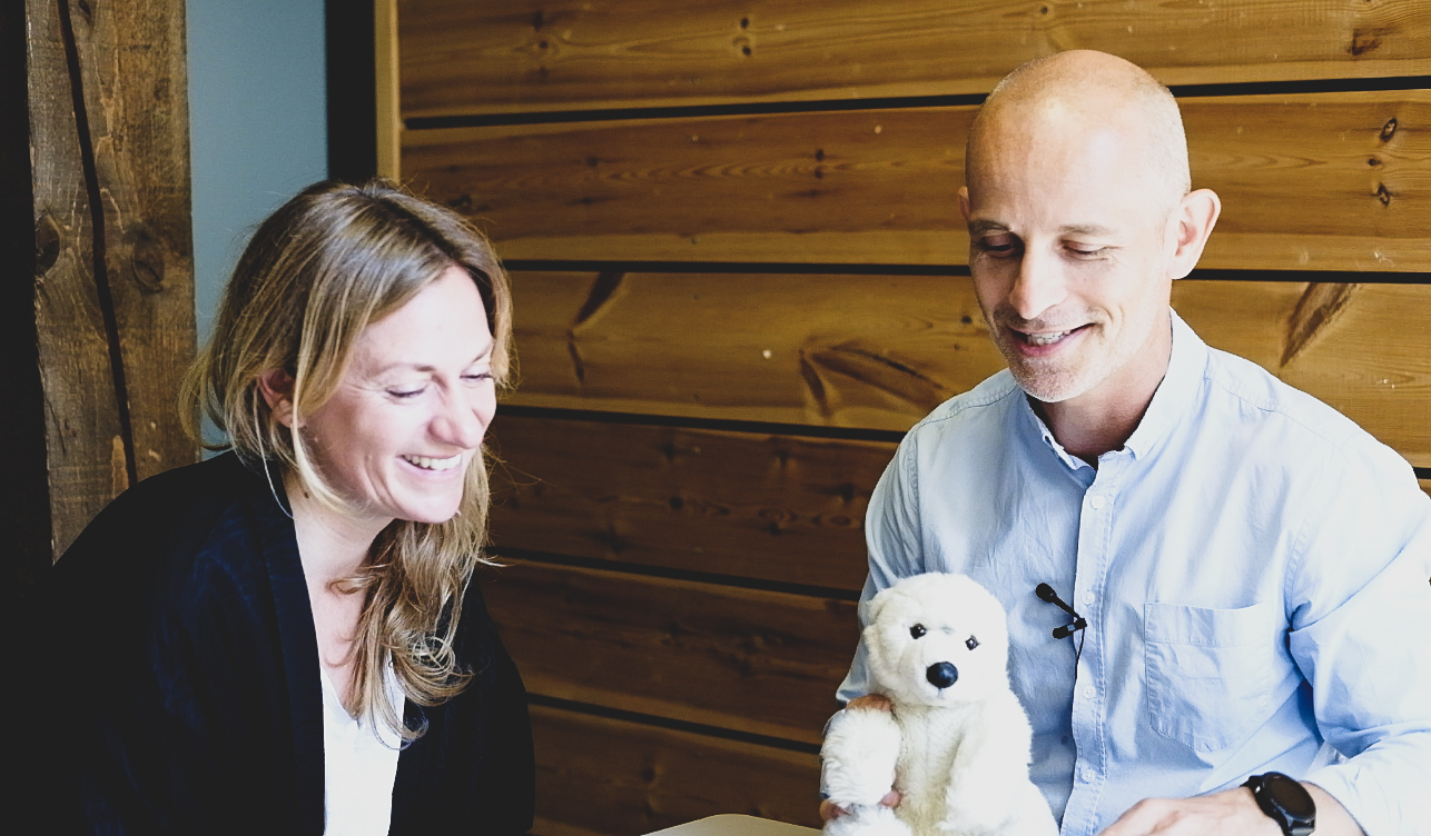 woman and man talking in office holding a polar bear teddy
